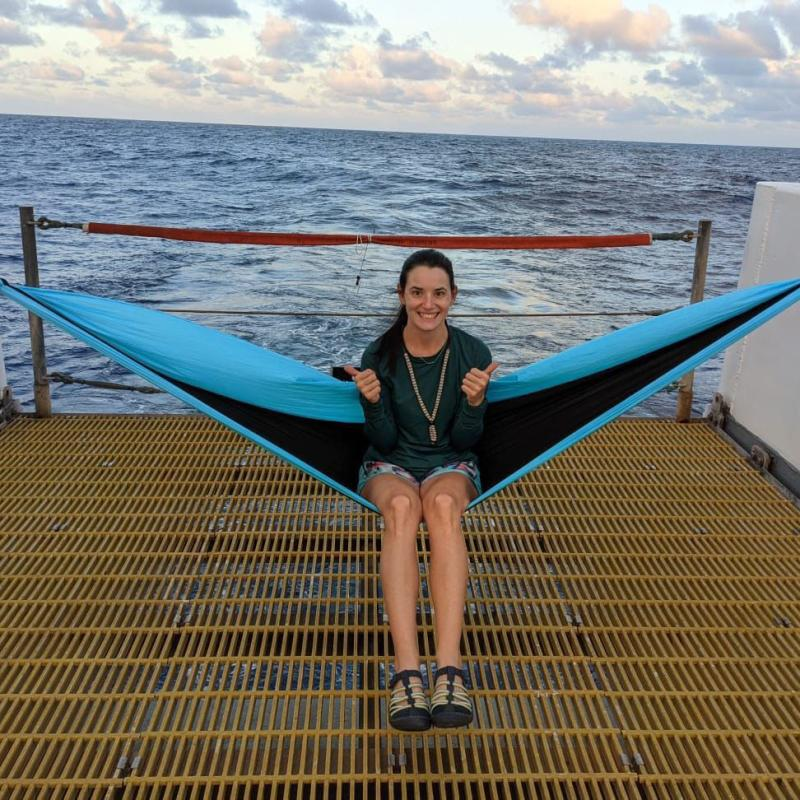 Mary Applegate sitting on a hammock set up on the aft deck of a ship.