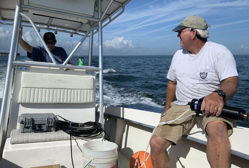 Two men are aboard a center-console boat. One drives, while the other holds scientific equipment.