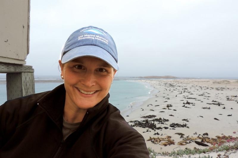 Woman wearing a cap looking a the camera with the shoreline visible in the background