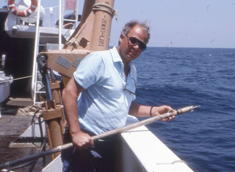 A scientist on the deck of a research ship at sea on a sunny day. He is holding a long pole with a sharp point at the end, used to insert tags into a shark's fin.