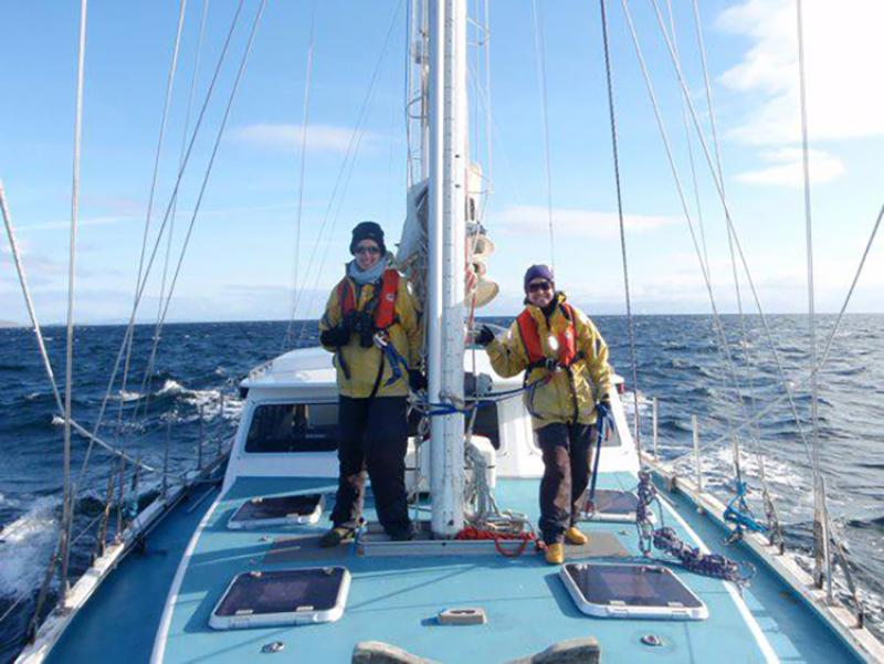 Two scientists stand on boat during marine mammal survey in Scotland