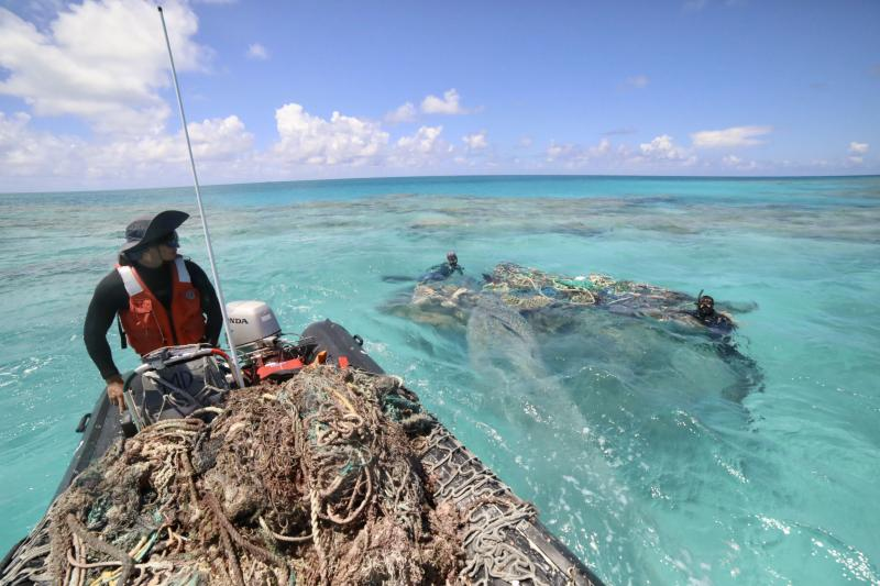 Coxswain William Reich and divers Rebecca Weible and Alika Garcia survey and find a large derelict fishing net at Kamokukamohoaliʻi (Maro Reef).