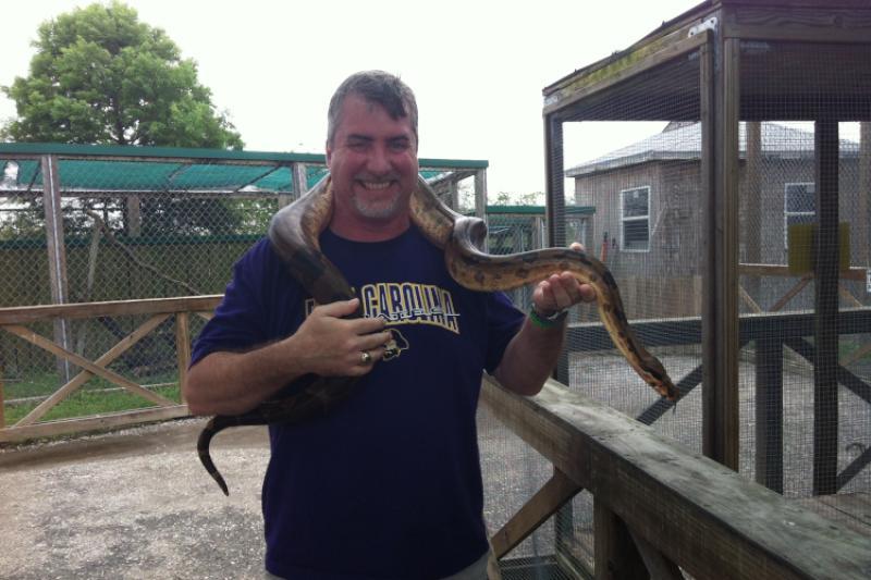 David Gloeckner holding a large constrictor snake.