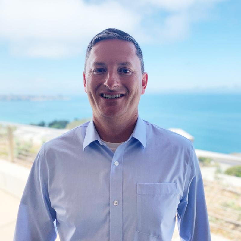 John Crofts wears a blue dress shirt and smiles at the camera with a sunny beach background.