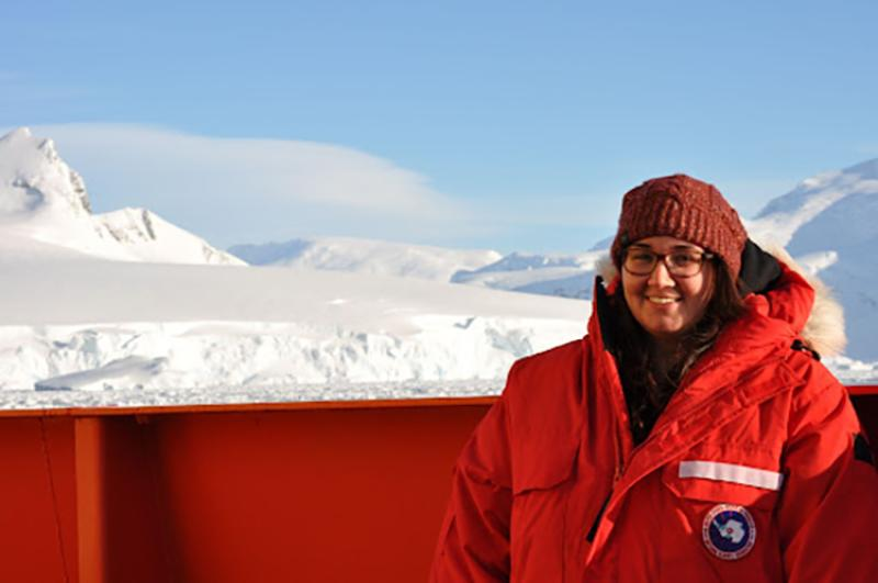 Zuzy Abdala stands in front of a glacier while conducting research in Antartica
