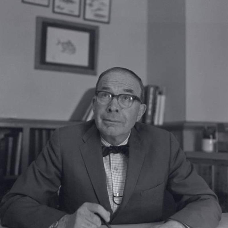 A black and whote photograph of a middle aged man at a desk with half-height bookcases filled with books in the background. The man wears glasses, a sport jacket with a light plaid shirt and dark, slender bow tie.