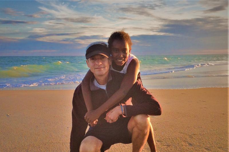 Todd Kellison on beach with his daughter, Bontu.