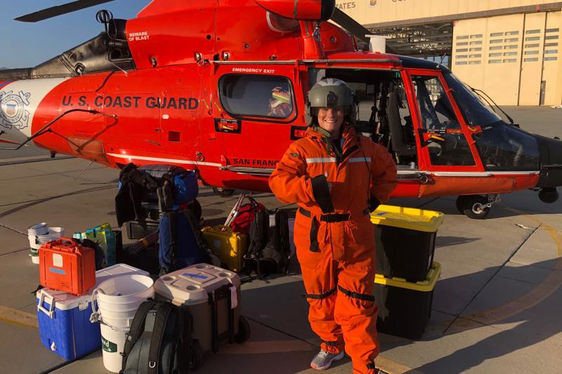 A woman scientist in flight gear in front of a U.S. Coast Guard helicopter.