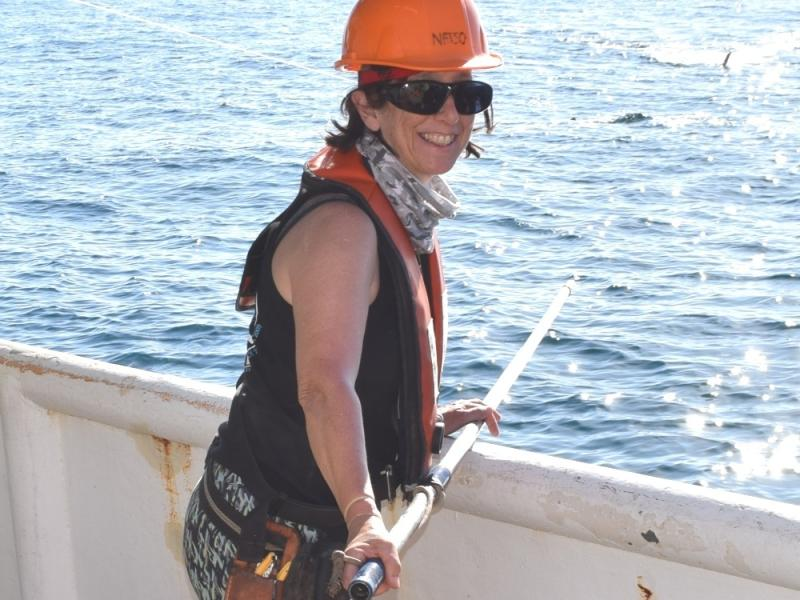 Lisa Natanson in hard hat and safety gear with shark tagging pole.