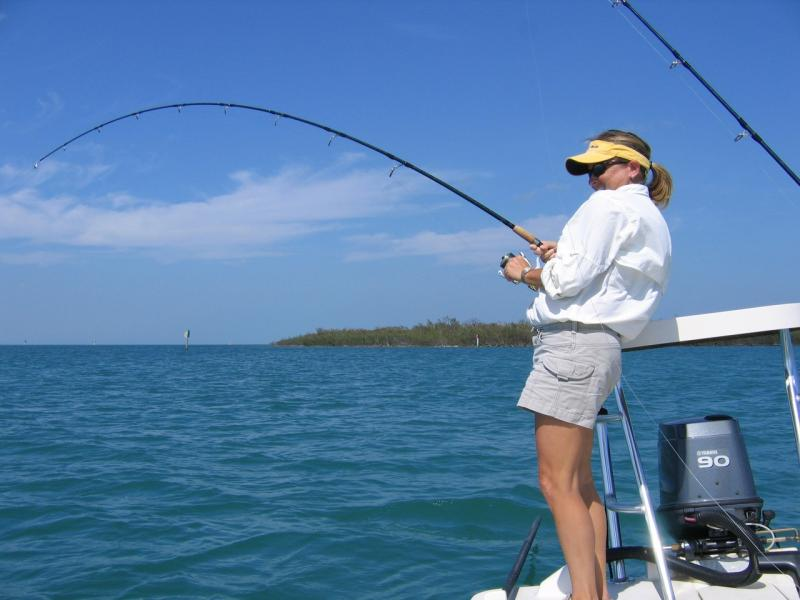Fishing in the Gulf of Mexico, women on the stern of a boat in shorts and visor.