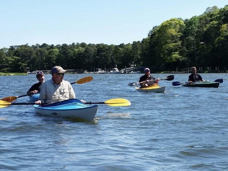 Four kayakers enjoying the water and sunshine.