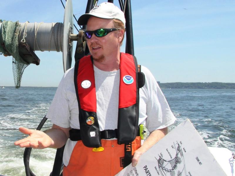 John Rosendale at the stern of Navoo with pfd and chart.