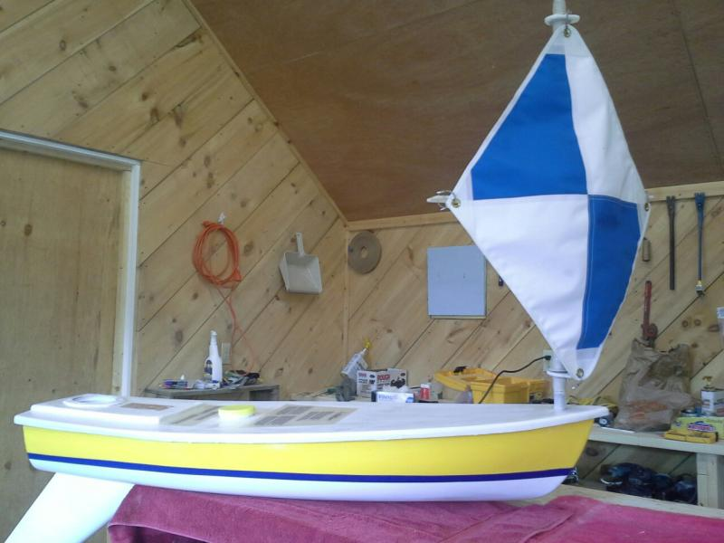 Yellow miniboat with blue and white sail on workbench.