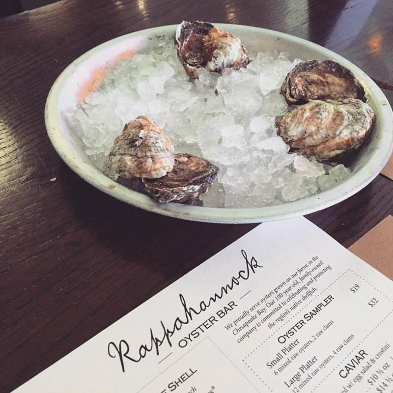 Raw oysters rest on a dish full of ice next to a Rappahannock Oyster Bar menu.