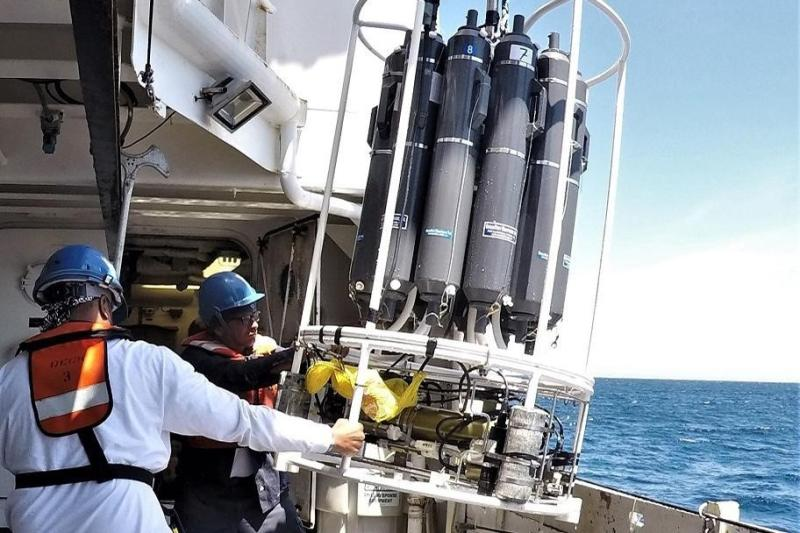 Two scientist pulling the CTD carousel back on board.