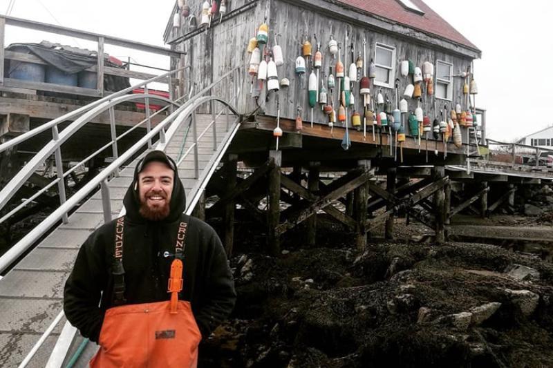 Zachary Fyke, in orange weather gear and black hoodie in front of lobster shack.